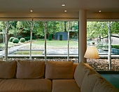 Upholstered sofa in front of floor-to-ceiling terrace windows with view into modern garden