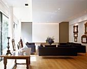 Schwarze Sofagarnitur und antiker ländlicher Holztisch im modernen Wohnraum