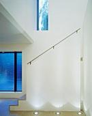 Nach oben offener Vorraum und Bodenstrahler vor weißem gemauertem Treppengeländer