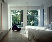 White bedroom with designer chaise longue in front of floor-to-ceiling terrace windows