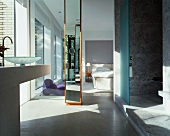 Ensuite bathroom with marble shower area and view of bed through ceiling-height doorway