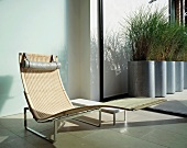 Designer rattan chaise longue in front of ceiling-height terrace door with view of planters