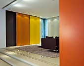 Colourful sliding walls in front of floor-to-ceiling windows in modern living space