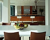 Wire fruit bowl on white dining table in front of open-plan designer kitchen