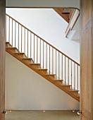 View of wooden stairs in modern stairwell through open door