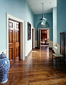Traditional hallway painted light blue with Chinese floor vase next to wooden double doors