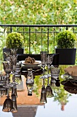 Various crystal glasses on reflective table in front of balcony with planters