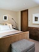 Hellgrauer Polsterhocker am Bettende eines Doppelbettes