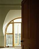 View of wooden balcony door through open door