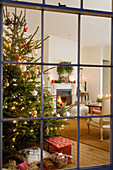 View of decorated Christmas tree in traditional setting through lattice window