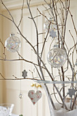 Christmas baubles and decorations hanging on twigs