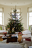 Decorated Christmas tree and armchairs with white upholstery in traditional interior