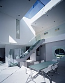 Open-plan, double-height dining area with stairs to upper storey
