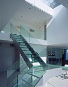Staircase with glass balustrade leading from living space to upper storey