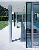 Concrete pillars on terrace in front of long glass wall