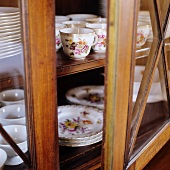Display cabinet with slightly open door and view of floral tea service