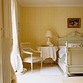 Stuhl im Rokokostil in Schlafzimmerecke vor Tapete mit weiss-gelben Streifen an Wand