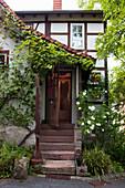 Altes Fachwerkhaus mit Treppenaufgang vor berankter Eingangstür