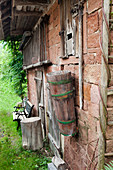 Garden bench against outer wall of brick shed with wooden trough hung on wall