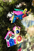 Colourful, sheet metal Christmas decorations on Christmas tree