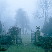 Misty atmosphere in park-like gardens with open wrought iron gate