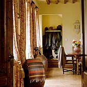 Grosse Amphoren vor Fenstern mit Vorhang und Sitzplatz vor einer Garderobennische
