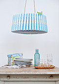 Pendant lamp with retro paper shade above stacked plates next to tray of glasses on kitchen table