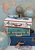 Stack of vintage suitcases, tin toy car and globes in front of a map