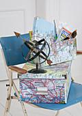 Schachteln mit Landkartenmotiv beklebt und stilisierter Globus aus Metallstreifen auf Vintage Stuhl
