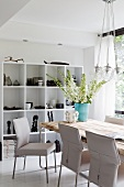 White, leather-covered chairs at modern table opposite shelving