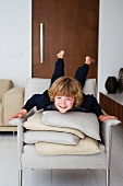 Child lying on stack of cushions on ecru armchair