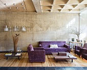Purple sofa set in living room with concrete wall and wooden floor