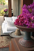 Bougainvillea flowers in wooden dish on wooden cabinet in front of spa swing bed