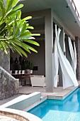 Überdachte Terrasse mit wehenden Vorhängen am Pool
