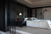 Elegant bedroom with black bamboo canes and thread curtains against walls around bed with white covers