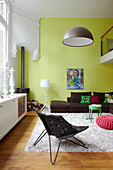 Furniture in a mix of styles and green walls in living room
