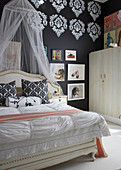 Bedroom in mixture of styles with pattern stencilled on black wall