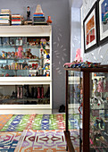 Collection of toys in display case and colourful rugs on floor