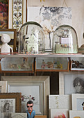 Tiny sculptures under bell jars and framed pictures on display cabinet