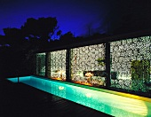 Terrace with swimming pool and view through of illuminated living room through curtains