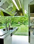Designerherd aus Edelstahl mit Dunstabzug vor Glasfront eines Wohnhauses mit Garten