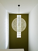 Spherical, designer pendant lamp made from pale mesh in front of green-painted wall with strip of glass bricks in stairwell