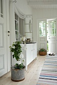 Potted plant next to white sideboard in loggia of white wooden house