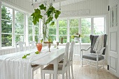 White dining table and chairs and reading chair in loggia of white wooden house