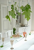 Silver wine goblets on white table cloth and candle chandelier decorated with plane tree leaves in white, country-house-style room