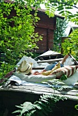 Woman lying comfortably on cushions in disused wooden boat in garden next to simple wooden house