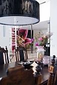 Englische Antikmöbel und moderne Hängelampe im Essbereich eines floral dekorierten Wohnhauses