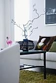 Buntes Flora- und Faunamuster auf schwarzem Grund an Wand und Sessel