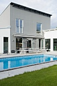 A swimming pool on the terrace of a modern house with a monopitch roof