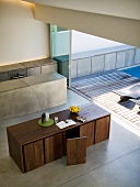 View from above of cubist, designer dining table and chairs and monolithic kitchen island in front of open sliding door leading to terrace with wooden deck and pool